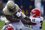Georgia inside linebacker Monty Rice (32) tries to strip the ball from Georgia Tech punter Pressley Harvin III (27) during the first half of an NCAA college football game Saturday, Nov. 30, 2019, in Atlanta. (Joshua L. Jones/Athens Banner-Herald via AP)