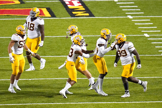 Minnesota players celebrate after defensive lineman DeAngelo Carter (99) intercepted a pass from Maryland quarterback Taulia Tagovailoa during the first half of an NCAA college football game, Friday, Oct. 30, 2020, in College Park, Md. (AP Photo/Julio Cortez)
