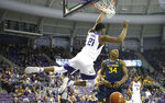 TCU center Kevin Samuel (21) hangs on the rim following his dunk as West Virginia forward Oscar Tshiebwe (34) looks on during the second half of an NCAA college basketball game, Saturday, Feb. 22, 2020 in Fort Worth, Texas. TCU won in overtime. (AP Photo/Ron Jenkins)