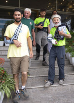The team leader, Tarcisio Bellò, 57, right, leaves a hotel with his colleagues to see the Italian ambassador in Islamabad, Pakistan, Thursday, June 20, 2019. The renowned Italian mountaineer, who narrowly survived along-with six other members of an expedition on a mountain, burst into tears Thursday when he recalled how helplessly he saw one of his Pakistani colleagues being swept away by an avalanche that struck them at an altitude of around 5,300 meters (17,390 feet) earlier this week. (AP Photo/B.K. Bangash)