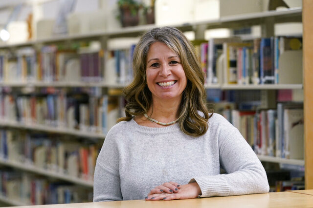 Middle-school counselor Shanon Baker poses for a photo in the school's library Wednesday, Nov. 18, 2020, in Sammamish, Wash. A master's degree and a full-time job weren't enough to help Baker land an apartment she could afford in Seattle's east-side suburbs. But a $750 million commitment by a partnership backed in part by Microsoft's affordable housing initiative helped do the trick. Urban Housing Ventures is cutting rents at 40% of the units in three buildings as part of an effort to make sure teachers, nurses and other middle-income professionals can live in the communities where they work. (AP Photo/Elaine Thompson)