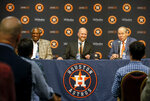 James Click, center, the newly-hired Houston Astros general manager, laughs with as Astros manager Dusty Baker, left, as Astros owner and chairman Jim Crane speaks about Click during a baseball press conference Tuesday, Feb. 4, 2020, at Minute Maid Park in Houston. (Jon Shapley/Houston Chronicle via AP)