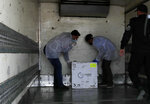 Medics check a shipment of the Russian Sputnik V vaccine inside a truck at the Kerem Shalom border crossing, in Rafah, Gaza Strip, Wednesday, Feb. 17, 2021. The Palestinian Authority said Wednesday that it dispatched the first shipment of coronavirus vaccines to the Hamas-ruled Gaza Strip, two days after accusing Israel of preventing it from sending the doses amid objections from some Israeli lawmakers. (AP Photo/Adel Hana)
