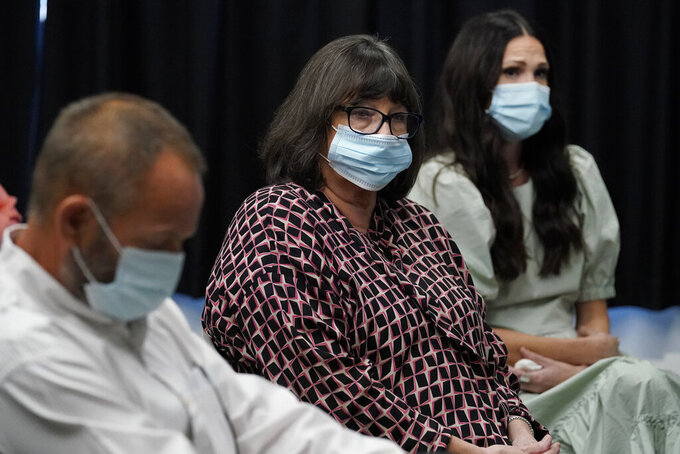 Megan Tobey, center, the sister of murder victim Paul Howell, sits with family members during a commutation hearing for his convicted killer, Julius Jones, Monday, Sept. 13, 2021, in Oklahoma City. Jones was convicted of the 1999 shooting death of Paul Howell and received the death penalty. The board voted that sentence be commuted to life in prison. (AP Photo/Sue Ogrocki)