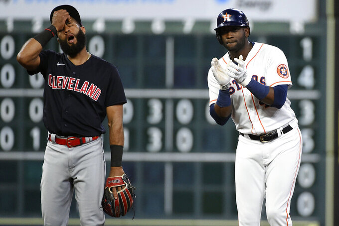 Houston Astros' Yordan Alvarez, right, reacts after hitting a two-run double, next to Cleveland Indians shortstop Amed Rosario during the fifth inning of a baseball game, Tuesday, July 20, 2021, in Houston. (AP Photo/Eric Christian Smith)