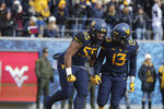 West Virginia linebacker Dante Stills (55) and defensive lineman Jeffery Pooler Jr. (13) celebrate a defensive stop during the first half of an NCAA college football game against TCU Saturday, Nov. 10, 2018, in Morgantown, W.Va. (AP Photo/Raymond Thompson)