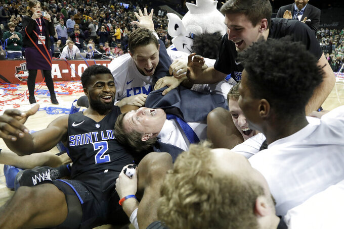 Saint Louis coach Travis Ford, center, celebrates with his team after a win over St. Bonaventure in an NCAA college basketball game in the final of the Atlantic 10 men's tournament Sunday, March 17, 2019, in New York. Saint Louis won 55-53. (AP Photo/Julio Cortez)