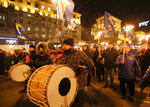 Activists of various nationalist parties play drums and carry torches during a rally in Kyiv, Ukraine, Wednesday, Jan. 1, 2020. The rally was organized to mark the birth anniversary of Stepan Bandera, founder of a rebel army that fought against the Soviet regime and who was assassinated in Germany in 1959. (AP Photo/Efrem Lukatsky)
