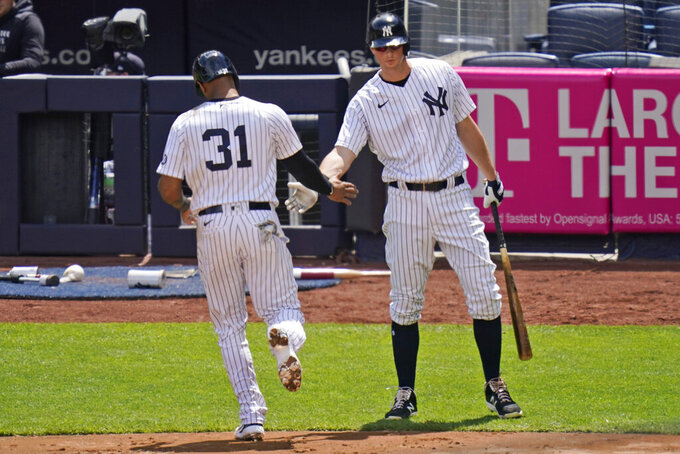 New York Yankees' DJ LeMahieu, right, greets Aaron Hicks, left, after he scored on a sacrifice fly hit by Brett Gardner during the second inning of a baseball game against the Detroit Tigers at Yankee Stadium, Sunday, May 2, 2021, in New York. (AP Photo/Seth Wenig)