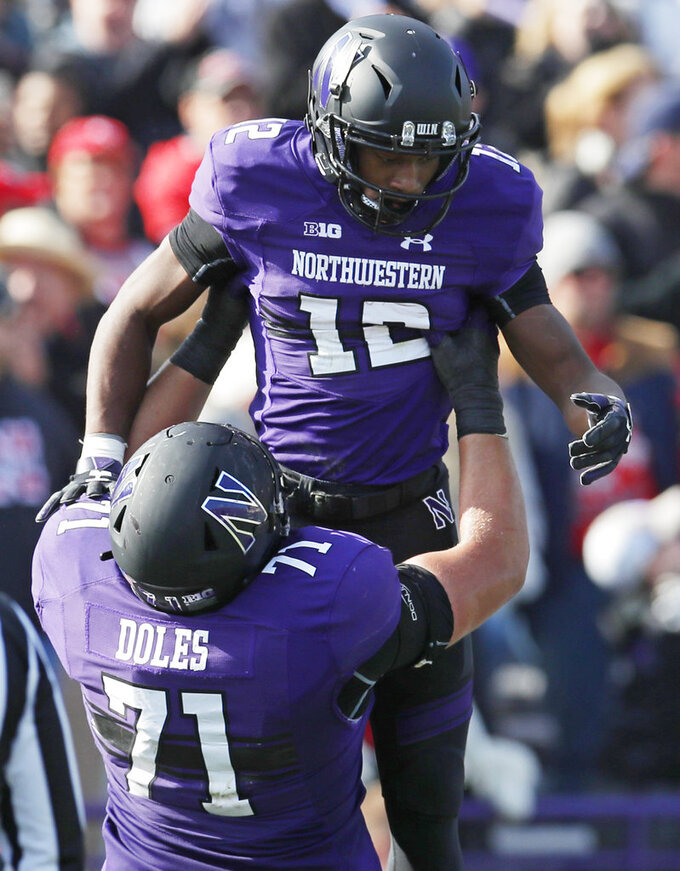 Northwestern's JJ Jefferson, top, is lifted in the air by teammate Tommy Doles as they celebrate a touchdown against Nebraska during the second half of an NCAA college football game Saturday, Oct. 13, 2018, in Evanston, Ill. (AP Photo/Jim Young)