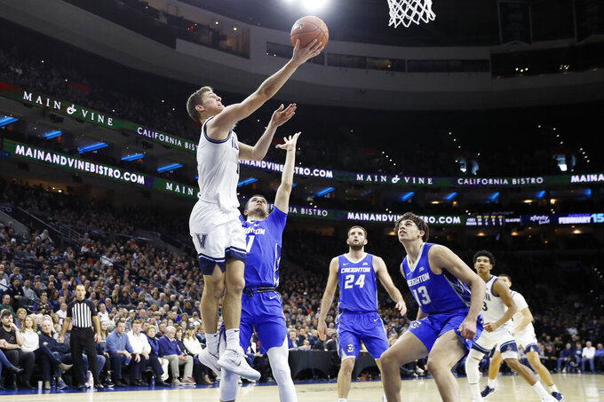 Villanova's Collin Gillespie, left, goes up for a shot over Creighton's Marcus Zegarowski during the first half of an NCAA college basketball game, Saturday, Feb. 1, 2020, in Philadelphia. (AP Photo/Matt Slocum)
