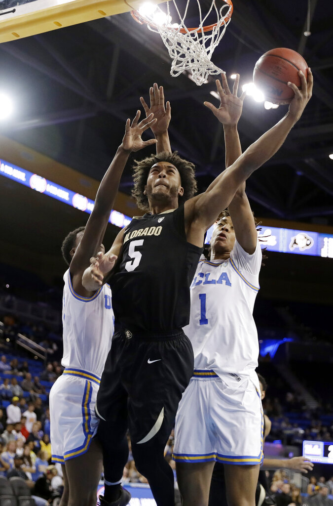 Colorado's D'Shawn Schwartz (5) scores between UCLA guard Kris Wilkes, left, and center Moses Brown (1) during the first half of an NCAA college basketball game Wednesday, Feb. 6, 2019, in Los Angeles. (AP Photo/Marcio Jose Sanchez)