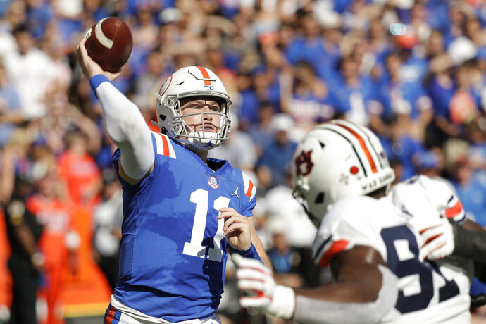 Florida quarterback Kyle Trask (11) throws a pass over Auburn defensive end Nick Coe (91) during the first half of an NCAA college football game, Saturday, Oct. 5, 2019, in Gainesville, Fla. (AP Photo/John Raoux)
