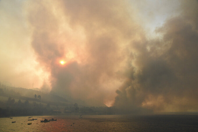 Smoke rises during a wildfire near Lampiri village, west of Patras, Greece, Saturday, Jul. 31, 2021. The fire, which started high up on a mountain slope, has moved dangerously close to seaside towns and the Fire Service has send a boat to help in a possible evacuation of people. (AP Photo/Andreas Alexopoulos)