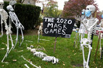 FILE - In this Oct. 22, 2020, file photo, coronavirus-themed Halloween decorations are displayed on a lawn in Tenafly, N.J. In a year when fear and death have commandeered front-row seats in American life, what does it mean to encounter Halloween, a holiday whose very existence hinges on turning fear and death into entertainment? (AP Photo/Seth Wenig, File)