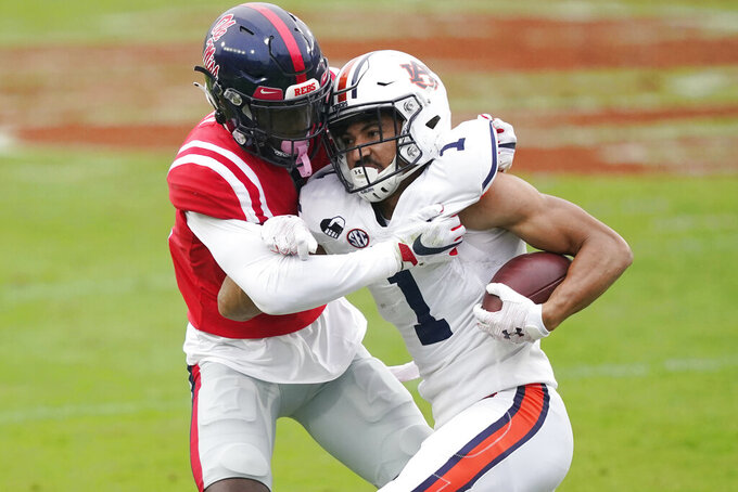 Auburn wide receiver Anthony Schwartz (1) tries to fight off a tackle by Mississippi defensive back A.J. Finley (21) after catching a pass during the first half of an NCAA college football game in Oxford, Miss., Saturday Oct. 24, 2020. (AP Photo/Rogelio V. Solis)