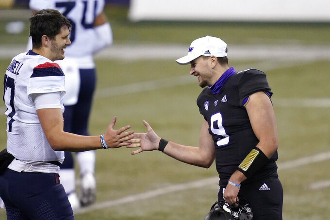 Washington quarterback Dylan Morris (9) greets Arizona quarterback Grant Gunnell after an NCAA college football game Saturday, Nov. 21, 2020, in Seattle. Washington won 44-27. (AP Photo/Elaine Thompson)