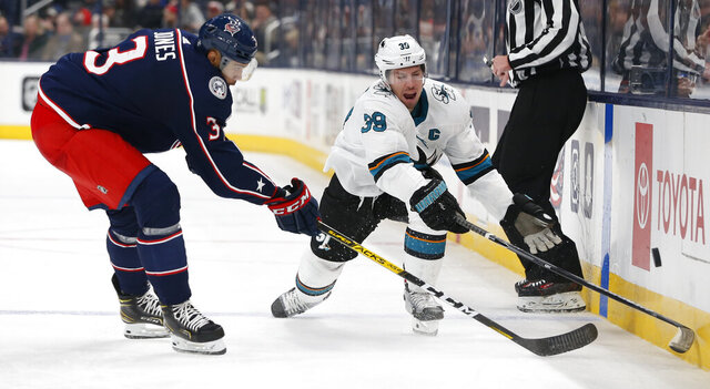 San Jose Sharks' Logan Couture, right, dumps the puck across the blue line past Columbus Blue Jackets' Seth Jones during the third period of an NHL hockey game, Saturday, Jan. 4, 2020, in Columbus, Ohio. The Sharks beat the Blue Jackets 3-2. (AP Photo/Jay LaPrete)