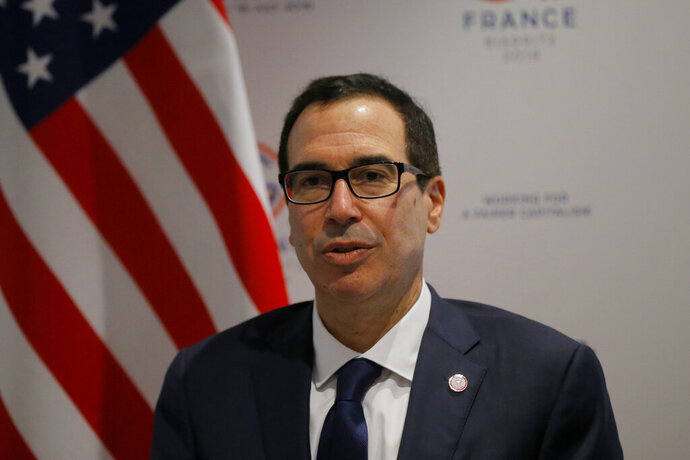 US Treasury Secretary Steve Mnuchin answers reporters after the G-7 Finance Thursday, July 18, 2019 in Chantilly, north of Paris. Top finance officials from the Group of Seven rich democracies are warning that cryptocurrencies like Facebook's Libra should not come into use before