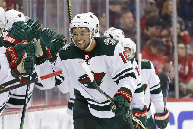 Minnesota Wild's Jordan Greenway celebrates with teammates after scoring a goal during the second period of an NHL hockey game against the New Jersey Devils Tuesday, Nov. 26, 2019, in Newark, N.J. (AP Photo/Frank Franklin II)