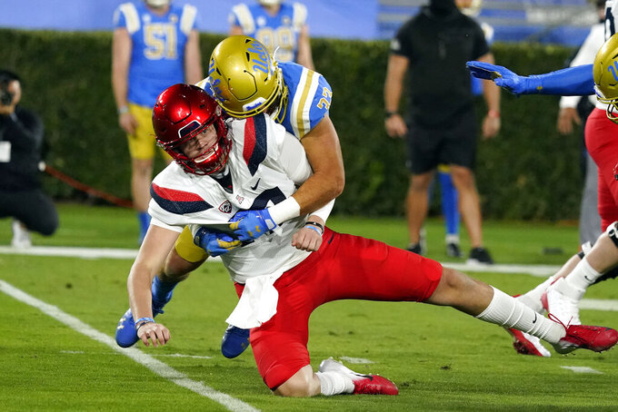 Arizona Wildcats quarterback Grant Gunnell, bottom, is tackled by UCLA linebacker Bo Calvert after throwing during the first half of an NCAA college football game Saturday, Nov. 28, 2020, in Pasadena, Calif. (AP Photo/Marcio Jose Sanchez)
