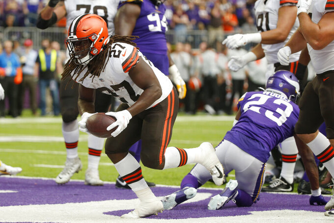 Cleveland Browns running back Kareem Hunt (27) scores on a 1-yard touchdown run ahead of Minnesota Vikings free safety Xavier Woods (23) during the first half of an NFL football game, Sunday, Oct. 3, 2021, in Minneapolis. (AP Photo/Bruce Kluckhohn)