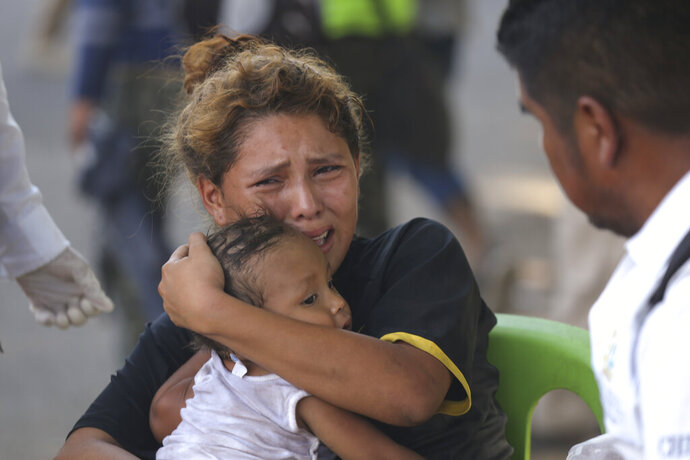 A migrant holds a child as Mexican National Guards block the passage of the group of migrants she is traveling with near Tapachula, Mexico, Thursday, Jan. 23, 2020. Hundreds of Central American migrants crossed the Suchiate River into Mexico from Guatemala Thursday after a days-long standoff with security forces. (AP Photo/Marco Ugarte)