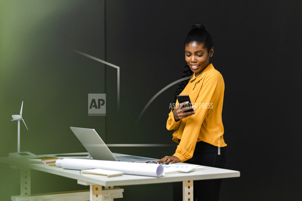 Businesswoman with laptop using mobile phone in studio