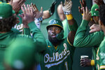 Oakland Athletics' Josh Harrison is congratulated after scoring against the Kansas City Royals during the first inning of a baseball game, Tuesday, Sept. 14, 2021 in Kansas City, Mo. (AP Photo/Reed Hoffmann)