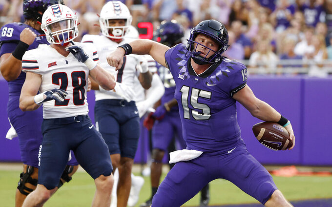 TCU quarterback Max Duggan (15) reacts after running the ball in for a touchdown as Duquesne defensive backs Spencer DeMedal (28) and Leandro Debrito (7) look on during the first half of an NCAA college football game Saturday, Sept. 4, 2021, in Fort Worth, Texas. (AP Photo/Ron Jenkins)