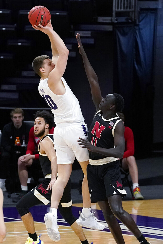 Northwestern forward Miller Kopp, left, shoots over Nebraska forward Lat Mayen during the first half of an NCAA college basketball game in Evanston, Ill., Sunday, March 7, 2021. (AP Photo/Nam Y. Huh)