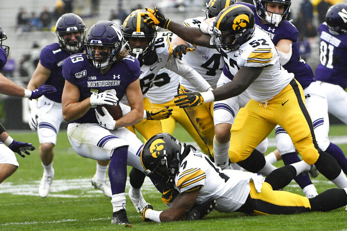 Northwestern wide receiver Riley Lees (19) is tackled by Iowa defensive back Devonte Young (17) and Iowa linebacker Amani Jones (52) during the second half of an NCAA college football game, Saturday, Oct. 26, 2019, in Evanston, Ill. (AP Photo/David Banks)