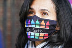 Homeris Soto, a para-professional with Mosaic Pre-K Center, wears a mask decorated with crayons as she greets students for the first day of school, Monday, Sept. 21, 2020, in New York. The city public schools delayed reopening for two weeks. (AP Photo/Mark Lennihan)