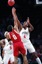 Richmond forward Nathan Cayo (4) defends Wisconsin guard D'Mitrik Trice (0) during the second half of an NCAA college basketball game in the Legends Classic, Monday, Nov. 25, 2019, in New York. Richmond defeated Wisconsin 62-52. (AP Photo/Kathy Willens)
