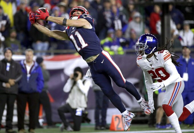 New England Patriots wide receiver Julian Edelman stretches out to catch a pass in front of New York Giants cornerback Janoris Jenkins, right, in the second half of an NFL football game, Thursday, Oct. 10, 2019, in Foxborough, Mass. (AP Photo/Elise Amendola)