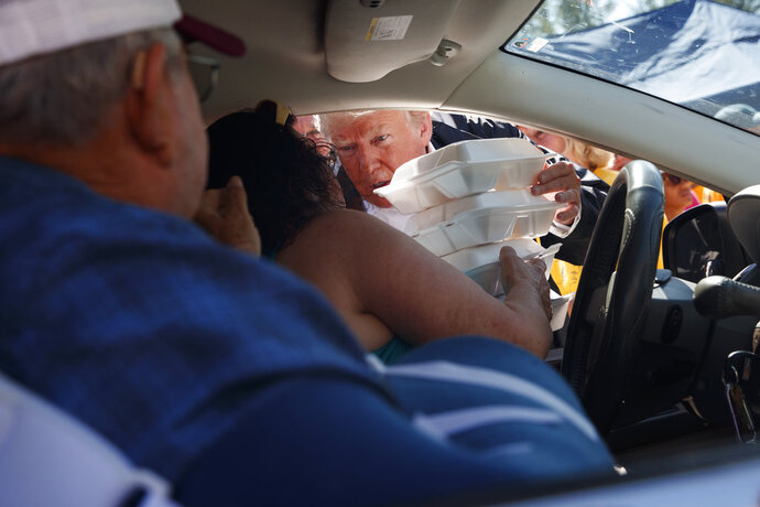 President Donald Trump hands out prepackaged meals at Temple Baptist Church in an area impacted by Hurricane Florence, Wednesday, Sept. 19, 2018, in New Bern, N.C. (AP Photo/Evan Vucci)