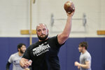 In this March 2, 2020, photo, former Nebraska football player Tanner Farmer and current wrestler for Concordia University throws a football during warmups before practice in Seward, Neb. A year ago Farmer was thought to be on the rise as an NFL draft prospect. Now he is wrestling.  (AP Photo/Nati Harnik)