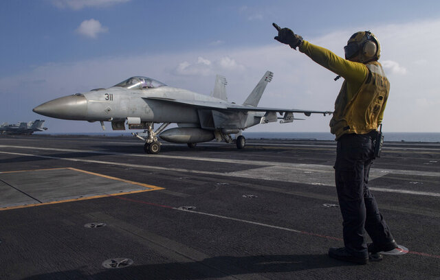 FILE - In this Nov. 27, 2020, file photo released by the U.S. Navy, Aviation Boatswain's Mate 3rd Class Marnell Maglasang, from La Puente, Calif., directs an F/A-18E Super Hornet on the flight deck of the aircraft carrier USS Nimitz in the Arabian Sea. The Pentagon announced Thursday, Dec. 31, 2020, that the USS Nimitz, the only Navy aircraft carrier operating in the Middle East, will return home to the U.S. West Coast. (Mass Communication Specialist 3rd Class Cheyenne Geletka/U.S. Navy via AP)