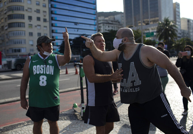 FILE - In this June 20, 2021 file photo, an activist, right, argues with a person who said the deaths related to COVID-19 are fake news, during a protest against Brazilian President Jair Bolsonaro and his handling of the COVID-19 pandemic, in Rio de Janeiro, Brazil. Less than 12% of Brazilians are fully vaccinated against the disease, more than 2,000 people are dying daily and experts warn Brazil may be entering its third wave. (AP Photo/Silvia Izquierdo, File)