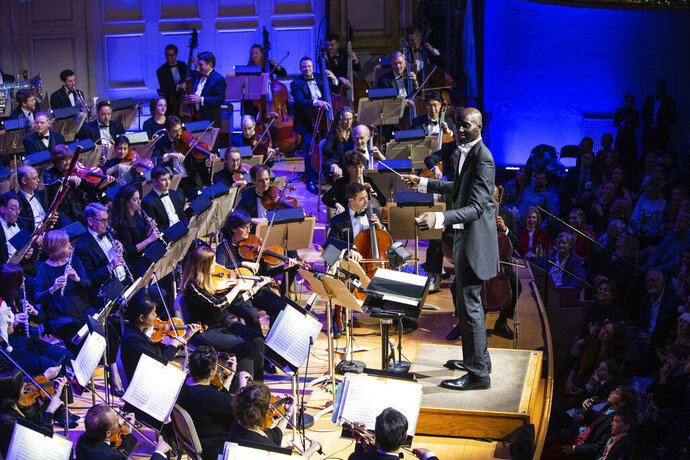 """In this Monday, Dec. 23, 2019, photo provided by Boston Pops, Boston Celtics player Tacko Fall makes his debut as a guest conductor during the renowned Boston Pops orchestra's holiday concert in Boston. The 7-foot-6 center took the stage to lead the orchestra in a rendition of the song """"Sleigh Ride"""