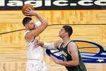 Orlando Magic center Nikola Vucevic, left, looks for a shot against Milwaukee Bucks center Brook Lopez during the first half of an NBA basketball game, Monday, Jan. 11, 2021, in Orlando, Fla. (AP Photo/John Raoux)