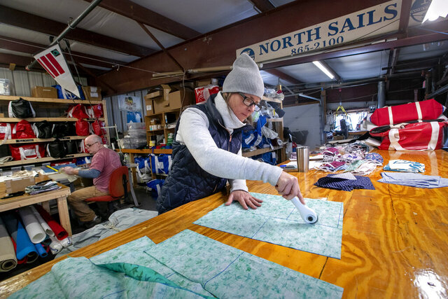 In this Monday, March 23, 2020, photo, Karen Haley cuts cotton fabric for masks to be given to caregivers during the coronavirus outbreak, at the North Sails shop in Freeport, Maine. The sail-maintenance business has converted part of its operation towards stitching masks instead of sails. Owner Eric Baldwin stitches masks in background. (AP Photo/Robert F. Bukaty)