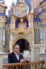 George Kalogridis, president of segment development and enrichment for Disney Parks, stands front of the Cinderella Castle at the Magic Kingdom theme park at Walt Disney World Monday, Aug. 30, 2021, in Lake Buena Vista, Fla. Kalogridis was one of 6,000 employees that was working at the theme park on opening day in 1971. (AP Photo/John Raoux)