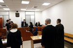 Israeli Prime Minister Benjamin Netanyahu, second right, stands while the judges enter the court room as his corruption trial opens at the Jerusalem District Court, Sunday, May 24, 2020.  He is the country's first sitting prime minister ever to go on trial, facing charges of fraud, breach of trust, and accepting bribes in a series of corruption cases stemming from ties to wealthy friends. (Ronen Zvulun/ Pool Photo via AP)