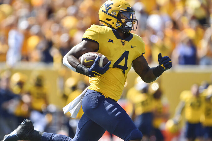 West Virginia running back Leddie Brown (4) rushes for a touchdown against Virginia Tech during the first half of an NCAA college football game in Morgantown, W.Va., Saturday, Sep. 18, 2021. (AP Photo/William Wotring)