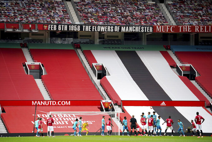 FILE - In this Saturday, July 4, 2020 file photo, empty stands are seen as Manchester United's Paul Pogba (6) shoots a free kick during their English Premier League soccer match against Bournemouth at Old Trafford stadium in Manchester, England. Much to the Premier League's dismay, the new season will start on Saturday, Sept. 12 just as the last one finished only 48 days earlier — in empty stadiums. The world's richest football league on Friday intensified its lobbying of the government to allow supporters back into games, even as England grapples with a sharp spike in coronavirus cases. (AP Photo/Dave Thompson, file)