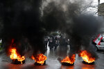 FILE - In this Feb. 19, 2021 file photo, relatives of victims of the Aug. 4, 2020 Beirut port explosion hold portraits of their loved one who were killed during the explosion, as they burn tires to block a road during a sit-in outside the Justice Palace, in Beirut, Lebanon. A public feud in recent weeks among prosecutors has starkly demonstrated how Lebanon's system of sectarian factions is paralyzing Lebanon's judicial system and snarling attempts to root out corruption. (AP Photo/Bilal Hussein, File)