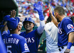 Texas Rangers' Shin-Soo Choo, center, is congratulated by teammates after hitting a solo home run during the first inning of a baseball game against the Houston Astros, Saturday, July 13, 2019, in Arlington, Texas. (AP Photo/Brandon Wade)