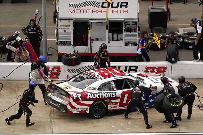NASCAR Xfinity Series driver Harrison Burton (20) gets service in the pits during the NASCAR Xfinity auto race in Richmond, Va., Saturday, Sept. 11, 2021. (AP Photo/Steve Helber)