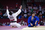 Lasha Bekauri of Georgia, left, reacts after defeating Eduard Trippel of Germany, right in the men -90kg final at the judo match of the 2020 Summer Olympics in Tokyo, Japan, Wednesday, July 28, 2021. (AP Photo/Vincent Thian)